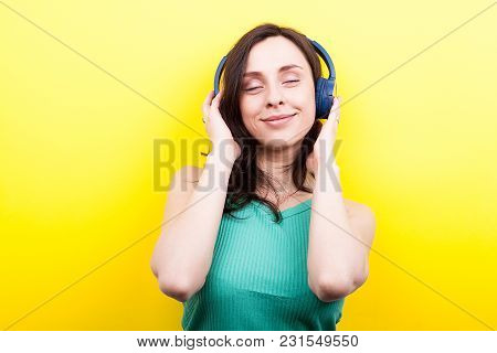 Young Woman With Her Eyes Closed Listening To Music Through Headphones On Yellow Background In Studi