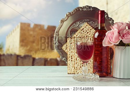 Passover Matzo And Wine On Wooden Vintage Table Over Old City Walls. Seder Plate With Hebrew Text Sa