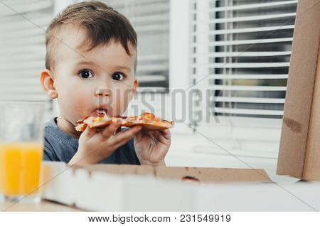 The Little Boy Eats A Huge Harmful Pizza Himself In The Kitchen And Drinks Juice, Very Fat And Harmf