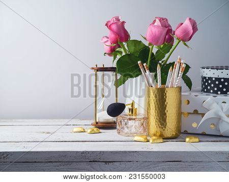 Office Desk With Pencils, Roses And Perfume Bottle. Feminine Workplace Concept.