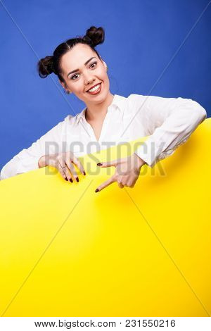 Happy Smiling Woman Poiting To A Yellow Banner With Copyspace Availabe Over Blue Background In Studi