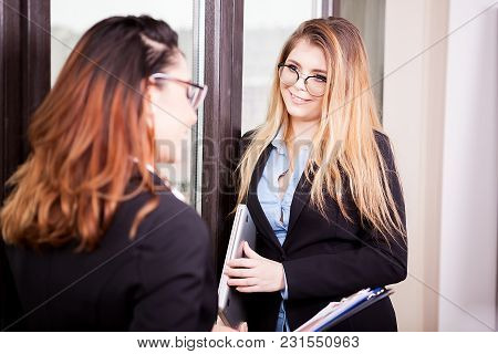 Two Businesswoman Talking To Each Other Near The Window