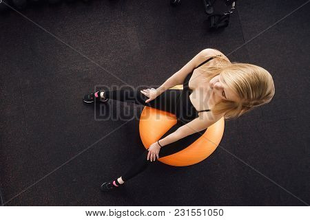 Seductive Blonde Woman, Dressed In Dark Fitness Clothing, Posing On Large Orange Exercise Ball In Fr