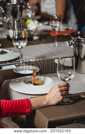 Woman Holds Glass Of White Wine. A Lot Of Different Wine Glasses On The Table At Wine Tasting. Peopl