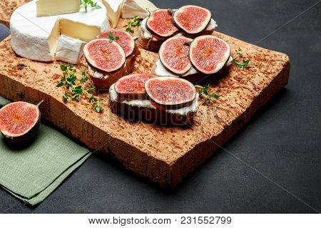 Bruschetta With Blue Cheese, Brie And Fresh Figs On Wooden Cork Cutting Board