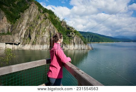 Brunette Female Tourist Looking Far Into The Distance Admiring Magnificent Views Of Green Rocky Moun