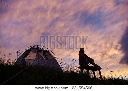 Female Tourist Jiker Sitting Near Her Tent On Top Of The Mountain Relaxing Enjoying Stunning Landsca