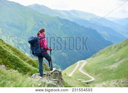 Female Traveller With A Backpack Resting On Top Of A Hill Looking Away At Transfagarasan Road Travel