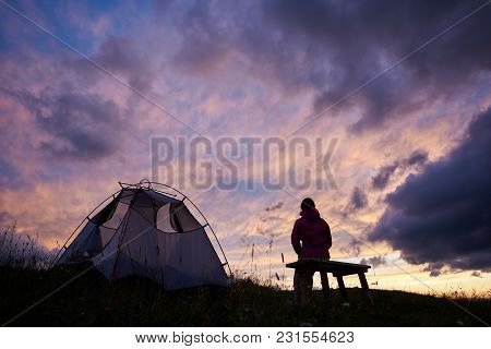 Hiker Woman Sitting On A Bench Near A Tent And Looking At Incredible View Of Sunset Evening Sky With