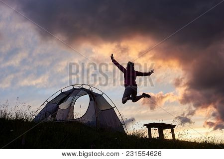 Happy Woman Jumping High Excitedly. Camping In The Mountains At Sunset Copyspace Tent Campsite Recre
