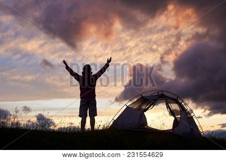 Silhouette Of Young Female With Her Hands Up Enjoying Beautiful Evening Sky Near Tent On Top Of Moun