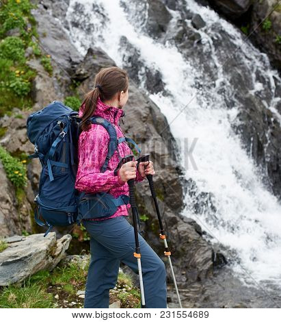 Hiker Girl In Modern Outfit With Blue Backpack Looking On A Big Waterfall. Young Hiker Woman In Pink