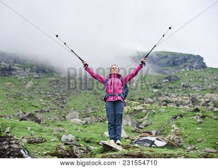 Beautiful Female Climber Lifting Hands Up In The Air With Walking Sticks In Hands While Standing On