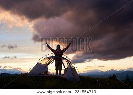 Happy Tourist Woman Standing Near The Tent With Raised Up Hands Enjoying View Of Mountains. Travel T