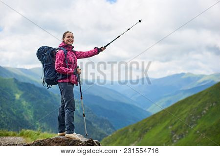 Hiking Girl With Trekking Sticks And A Backpack Stands On A Rock With A Blurred Background Of The Mi