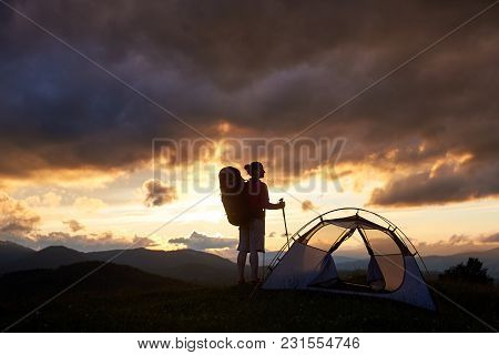 Horizontal Shot Of A Silhouette Of A Female Backpacker Standing Near Her Tent In The Mountains Obser