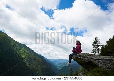 Profile Of The Girl Sitting On The Rock, Dangling Her Legs In The Abyss Against The Backdrop Of Gree