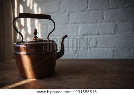Old Copper Kettle On The Wooden Table .