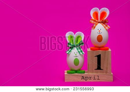 Multicolored Funny Eggs In The Form Of Cute Bunny With Wooden Calendar Set On 1 April Isolated On Pi