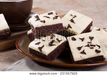 Closeup Of A Pile Of Chocolate Fudge Brownies On A Plate With A Coffee Cup In Background