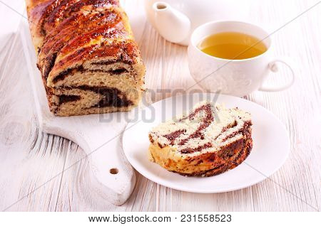 Slice Of Braided Loaf With Filling And Cup Of Tea