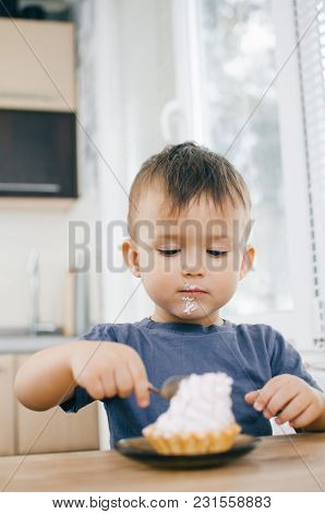 The Child In The Kitchen Eating A Cake With Cream Is Very Appetizing, Spoon