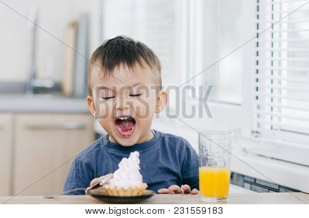 A Child In The Kitchen Eats Cake And Screams With Delight