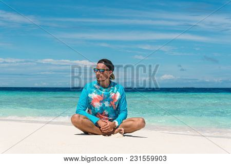 Man Sit On Sandy Beach With Pure Transparent Water Of Ocean In Maldives
