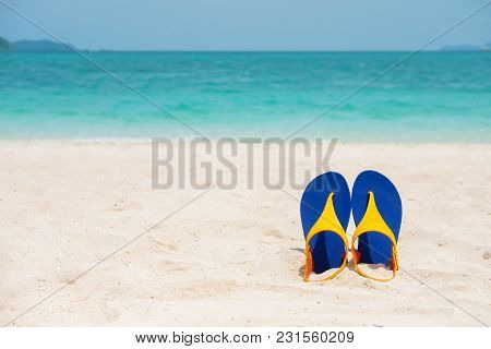 Beach Sandals On The Sandy Sea Coast, Summer Concept Holiday And Vacation Concept. Tropical Sea.