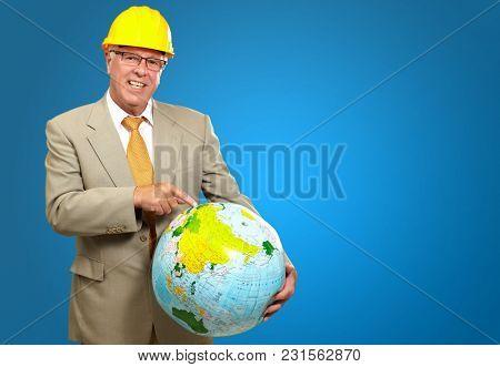 Happy Male Architect Pointing On Globe Isolated On Blue Background