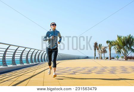 Girl Running On The Boardwalk For A Workout By The Sea