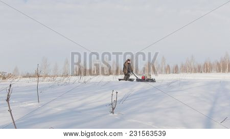 Man In Winter Clothes Fast Riding And Maneuvering On Mini Snowmobile On Deep Snowdrifts, Specialized