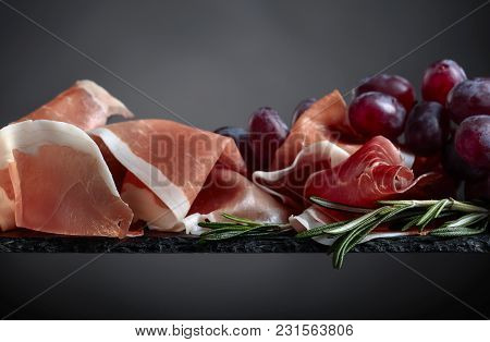 Prosciutto With Grapes And Rosemary On A Black Background.