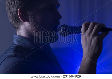 Photo Of Man Singing To The Microphone With Blue Lights In The Background