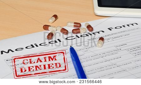 Medical Claim Form On A Wooden Surface. Near Leather Wallet, Fountain Pen Blue, Mobile Phone. On The