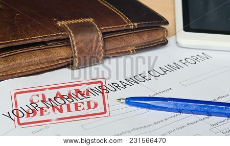Your Mobile Insurance Claim Form On A Wooden Surface. Near Leather Wallet, Fountain Pen Blue, Mobile