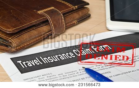Travel Insurance Claim Form On A Wooden Surface. Near Leather Wallet, Fountain Pen Blue, Mobile Phon