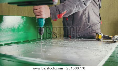 Close - Up Of Drill Running By Worker's Hands And Drilling Metal Plate