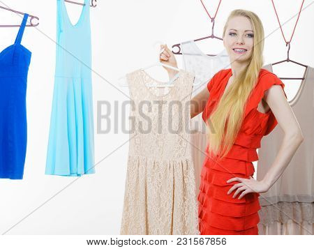 Young Blonde Long Hair Woman In Clothes In Shop Or Wardrobe Choosing Summer Outfit, Dresses Hanging