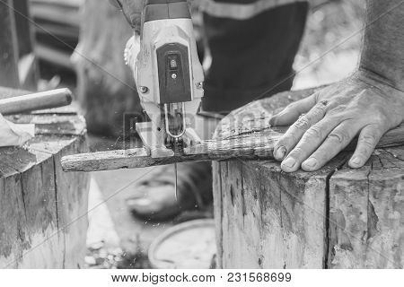 Man With Protection Gloves Using An Electric Saw To Cut A Plank