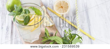 Fresh Homemade Lemonade In Glass With Ice And Mint, Ingredients For Cocktail, Lemon And Lime Slices,