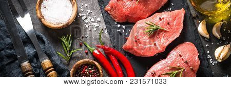Raw Meat. Fresh Beef Steak With Rosemary And Spices On Black Background. Long Banner Format.
