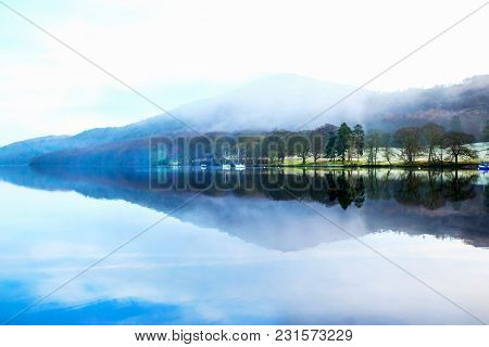 Lake Windermere, Lake District, Uk, Early Morning View Across The Flat Calm Lake Forming A Complete