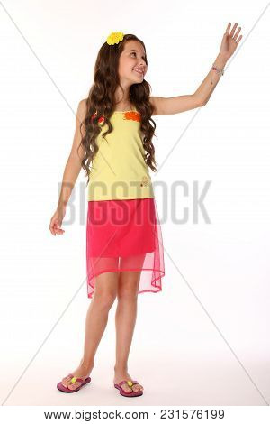 Pretty Brunette Slender Child With Chic Long Hair Is Artistically Posing Full-length In A Red Skirt