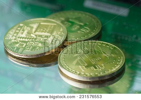 Three Golden Bitcoins On Printed Circuit Background
