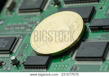 Golden Bitcoin On Green Printed Circuit Board With Microchips