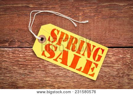 spring sale sign - red stencil text on a yellow paper price tag against grunge wood