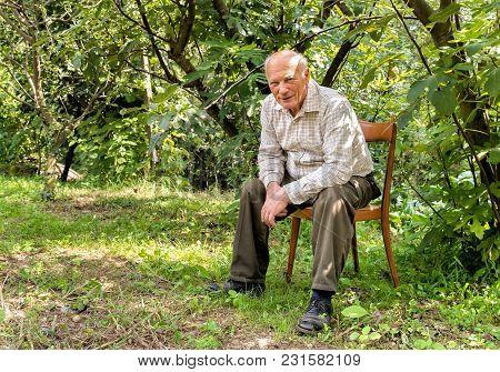 Senior Man Sitting On A Chair In The Garden.