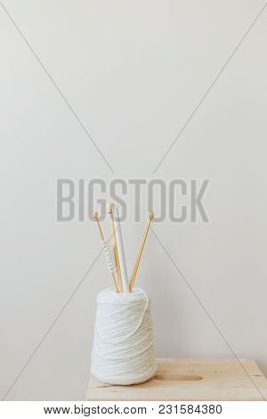 Spool Of Yarn And Knitting Needles Background Of Beige Wall