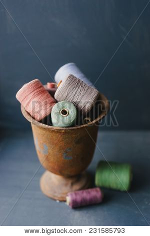 Multicolored Vintage Thread Bobbins In A Rusty Cup On A Blue Background